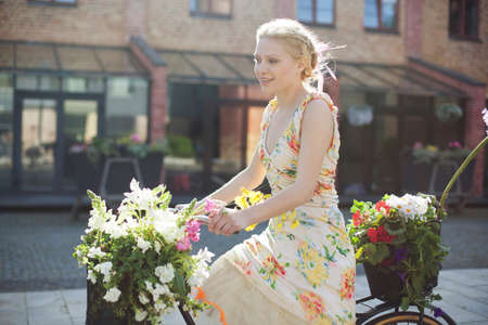 Young woman cycling along road, carrying flowers in baskets on bike LANG_EVOIMAGES