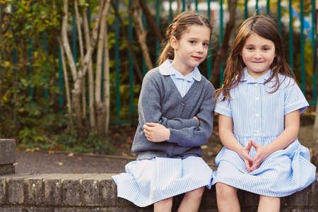 Portrait of two elementary schoolgirls in school playground LANG_EVOIMAGES
