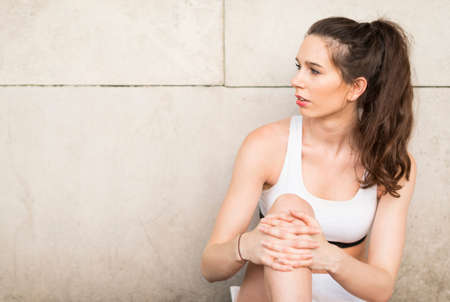 Young female runner leaning against wall looking sideways