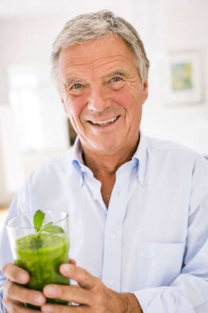 Portrait of senior man with green vegetable smoothie in kitchen