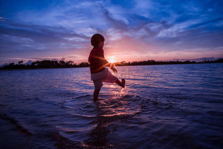 Young boy paddling in sea, sunset