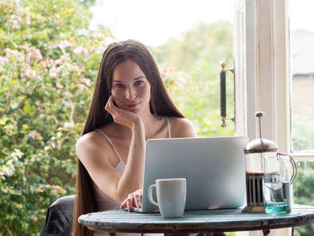 Portrait of young woman sitting at table, coffee and laptop in front of her