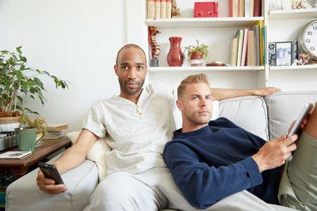 Homosexual couple relaxing together on sofa looking away LANG_EVOIMAGES