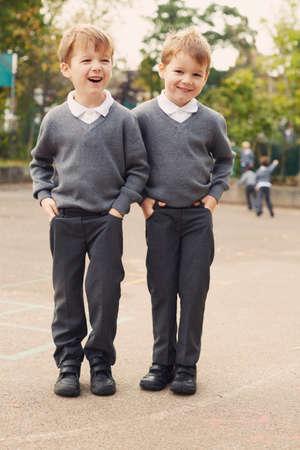 Portrait of elementary schoolboy twins in playground