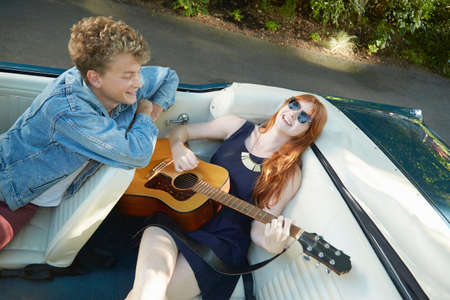 Young woman playing guitar for boyfriend in back seat of vintage convertible