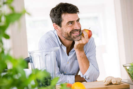 Mature man eating apple at kitchen counter