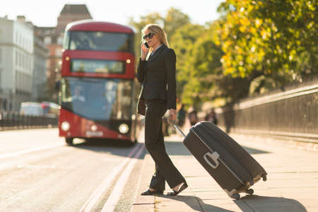 sidewalk talk: Young businesswoman with wheeled suitcase talking on smartphone, London, UK LANG_EVOIMAGES