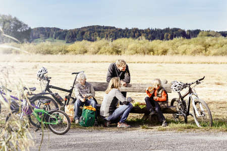 Family with bicycles resting on bench by roadside