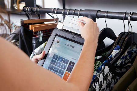 materialism: Mature woman using digital tablet to charge customer credit card in fashion boutique LANG_EVOIMAGES