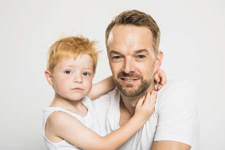 Studio portrait of boy with arms around his father LANG_EVOIMAGES