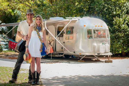 Portrait of couple in front of their converted boutique airstream trailer