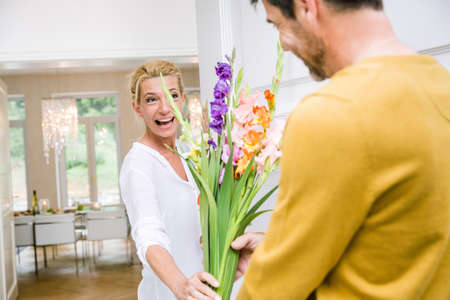 Romantic mature man handing bunch of flowers to wife in dining room LANG_EVOIMAGES