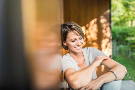 Mature woman relaxing outside house LANG_EVOIMAGES