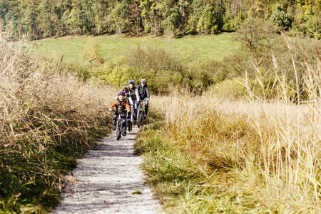 Front view of family cycling on rural path