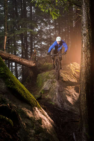 athletic wear: Young male mountain biker riding over forest boulders LANG_EVOIMAGES