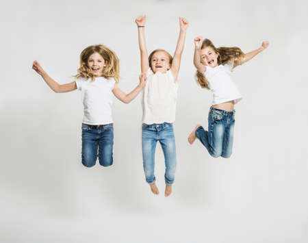Studio portrait of three girls jumping mid air LANG_EVOIMAGES