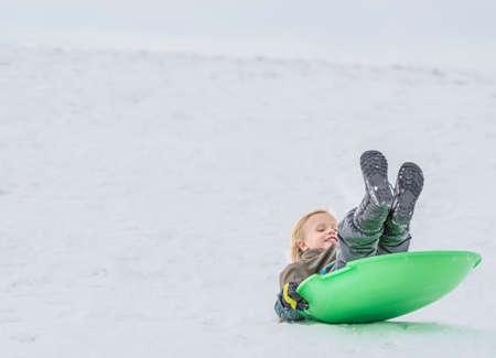 to go sledding: Boy playing on toboggan in snow