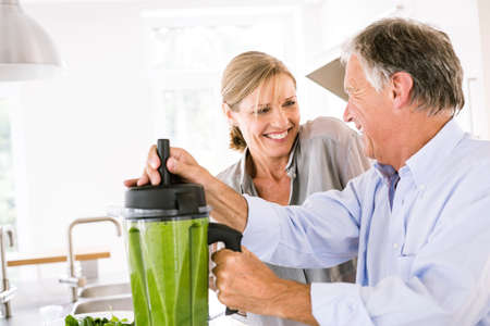54: Couple preparing green vegetable smoothie in kitchen LANG_EVOIMAGES