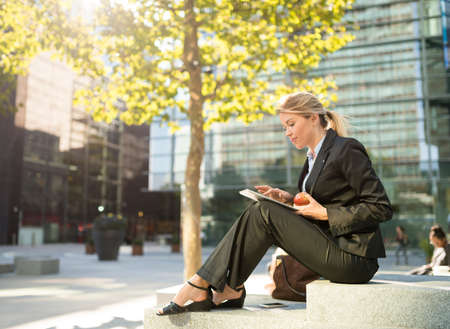 handheld device: Young businesswoman sitting outside city office using digital tablet