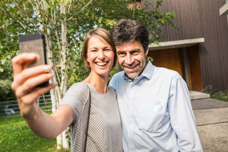 Mature couple posing for selfie outside new house