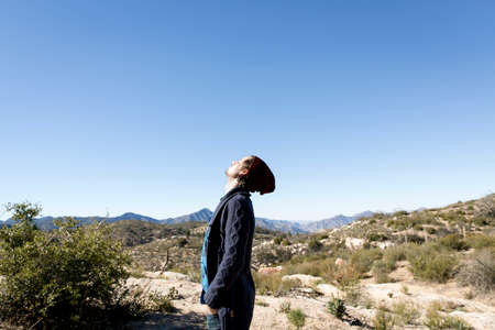 Side view of young woman wearing knit hat, hands in pockets looking up, Chilao Campgrounds, Los Angeles, California, USA