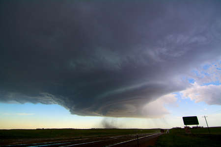 environmental issues: Rotating supercell storm over highway, with streaks indicating falling hail, southeast of Scottsbluff, Nebraska, USA