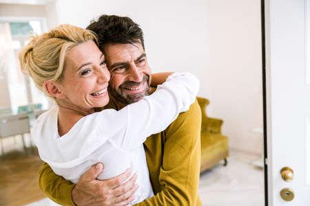 Romantic mature couple hugging in dining room