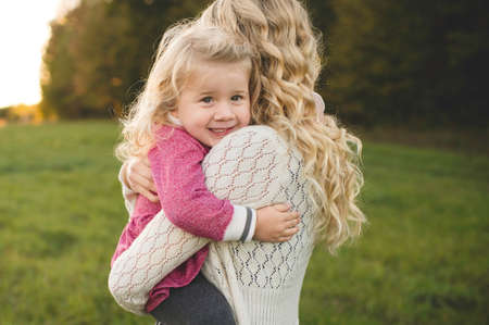 Portrait of mid adult woman hugging daughter in field LANG_EVOIMAGES