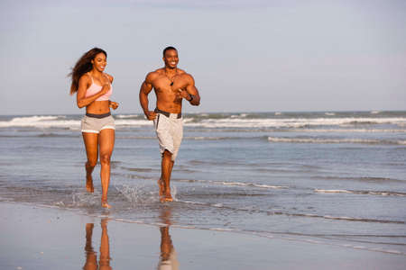 Couple running along beach, smiling LANG_EVOIMAGES