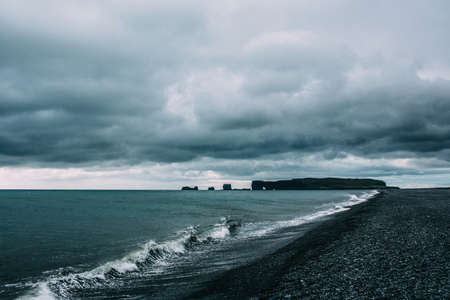 Ocean waves on coastline under dramatic sky, Vik, Iceland LANG_EVOIMAGES