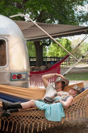 Couple reclining on hammock next to converted boutique airstream trailer LANG_EVOIMAGES