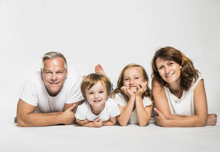 Studio portrait of parents lying on their front with son and daughter LANG_EVOIMAGES