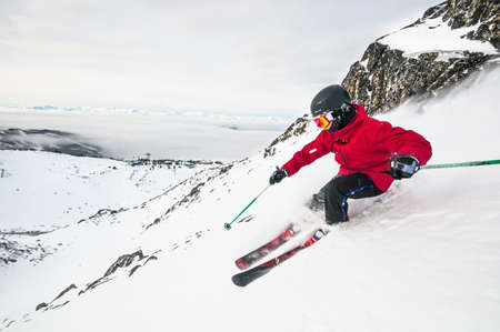 gifted: Side view of young man skiing down snowy mountain, Whistler Blackcomb ski resort, British Columbia, Canada LANG_EVOIMAGES