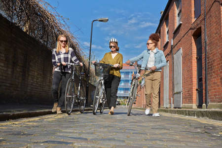 Low angle full length front  view of women pushing bicyles on cobblestone road
