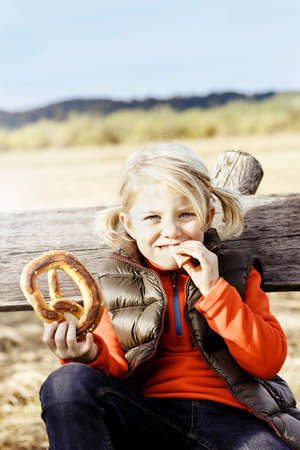 Girl outdoors eating pretzel looking at camera smiling