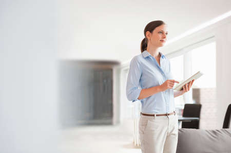Woman using digital tablet to control  home automation system in modern living room