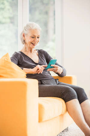 Senior woman taking a break from exercising using smartphone on living room sofa LANG_EVOIMAGES