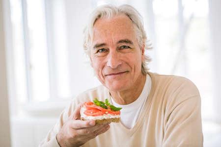 Senior man eating open sandwich in kitchen