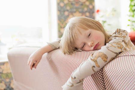 tiredness: Portrait of sleepy boy leaning on living room sofa
