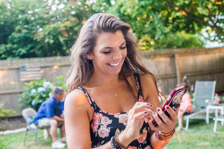 Woman texting on smartphone at party in garden