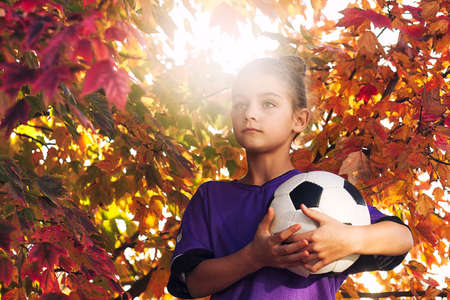Girls by tree covered in autum leaves holding football looking away LANG_EVOIMAGES