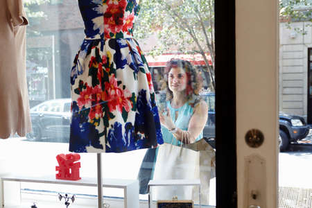 customer facing: Mature woman looking in window of fashion boutique