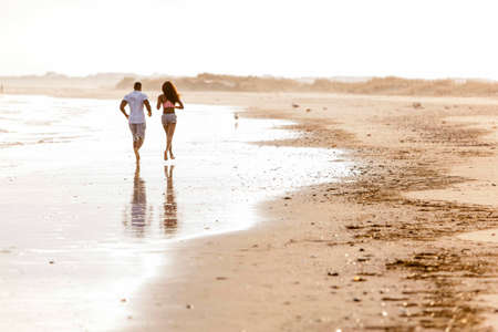 Couple running along beach, rear view LANG_EVOIMAGES