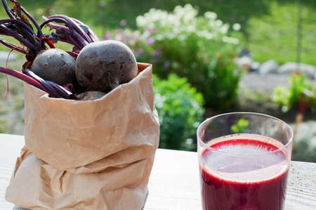 Bag of organic beetroot and glass of beetroot juice on garden table