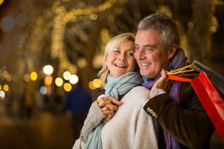 christmas spending: Portrait of mature couple with xmas shopping on tree lined avenue, Majorca, Spain