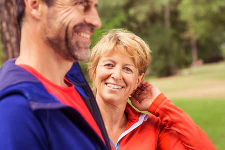 Couple wearing sports clothing, outdoors, smiling