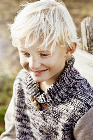 Portrait of blonde boy looking down smiling
