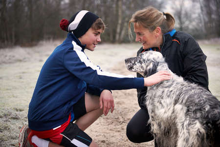Mother and son crouching down stroking dog, face to face smiling