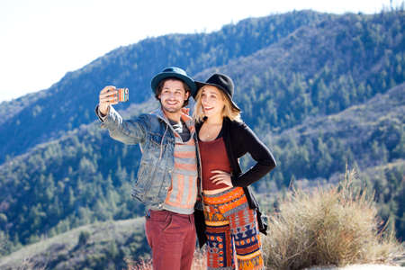 Young couple using smartphone to take selfie in front of mountain range, Chilao Campgrounds, Los Angeles, California, USA