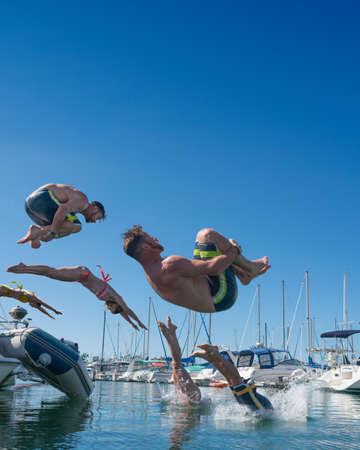 Digitally multiplied people diving and somersaulting into sea